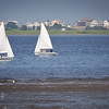 BRYAN EATON/Staff photo. Sailboaters catch an east wind in the Merrimack River at low tide in a view from Joppa Park on Wednesday afternoon. The weather for boating should generally be good into the weekend though there is a chance of showers with the humid weather.
