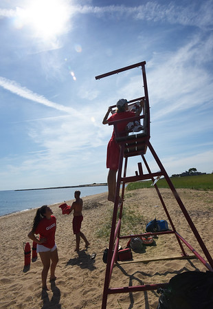 BRYAN EATON/Staff photo. Lifeguard Jake Greco arranges an awning on the lifeguard stand along the Merrimack River in Newburyport as Grace Shelley, left, and senior guard Drew Brewer get ready for their shift.