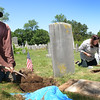 BRYAN EATON/Staff photo. Josh Gerloff digs to the base of a broken gravestone while Rachel Mayer uses a solution to clean off a stone at the Newbury First Parish Burying Ground.