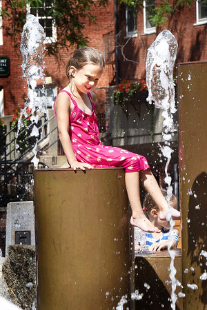 BRYAN EATON/Staff photo. Ella Caldwell, 5, sits on the fountain on Inn Street in Newburyport on a visit with her sister, Cecelia, 7, and grandmother Deann Boulay on Monday afternoon. The fountain had been closed several days due to a minor leak.