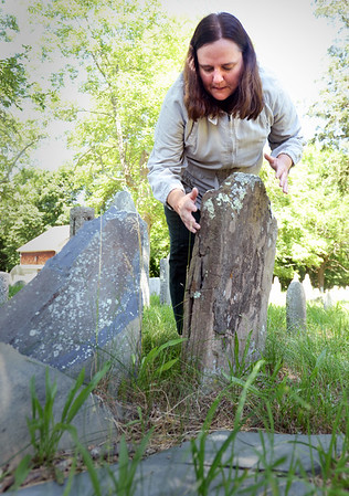 BRYAN EATON/Staff photo. Rachel Mayer checks the condition of a slate gravestone at the Newbury First Parish Burying Ground.