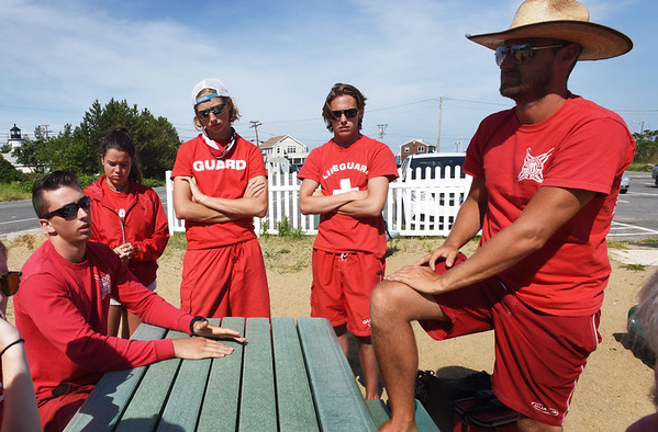 BRYAN EATON/Staff photo. Matthew Hayden, left, who made a life-saving rescue last year and other guards meeting before heading out to their posts on the Newburyport end of Plum Island.
