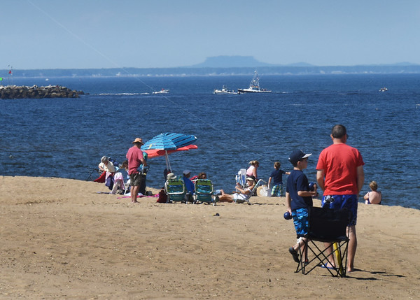 BRYAN EATON/Staff photo. Mt. Agamenticus in southern Maine can be seen rising above beach-goers to Plum Island on Wednesday afternoon.