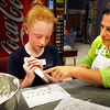 BRYAN EATON/Staff photo. Marion Cipolle shows Emma Callahan, 12, how to hold and use a pastry bag to create basic designs in a cake decorating class, one of the Amesbury Youth Recreation's summer classes. In the week-long class, Cipolle, a professional baker, will teach them how to make Buttercream and Royal icings, make frosty flowers, and create decorations with candies and melted chocolate.