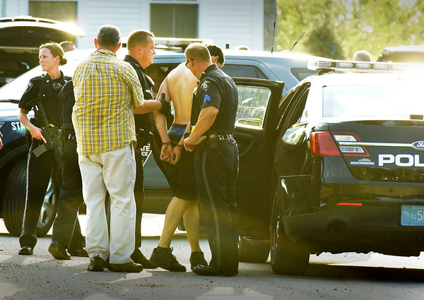 BRYAN EATON/Staff photo. Police put the suspect into an awaiting cruiser after he led them on a chase through backyards from the Port Plaza area. He was found in a house under construction on the new development Wright's Court which is off Toppan's Lane near Pettingell Park at Newburyport High School.