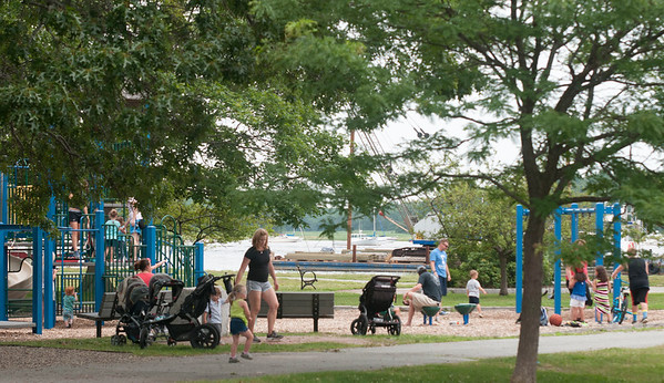 JIM VAIKNORAS/Staff photo Boats in the Merrimack River float in the background as families enjoy the playground at Cashman Park in Newburyport Saturday morning.