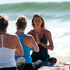 JIM VAIKNORAS/Staff photo Yoga instructor Sarah Oleson teaches a drop in class on Salisbury Beach Sunday on a warm July morning. Claases take place every day at 8am right behind the stage at the beach center.