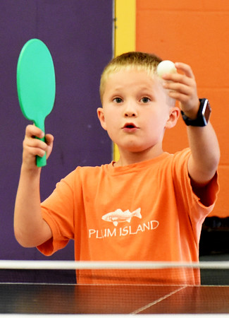 BRYAN EATON/Staff photo. Nathan Rollins, 6, of Merrimac readies for a serve in a ping pong game with Otto Severino, 7, of Newburyport on Monday afternoon. They were at the Boys and Girls Club in Salisbury where all activities were inside due to the rain.