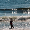 JIM VAIKNORAS/Staff photo A woman stands in shallow water as the tide come in on Salisbury Beach early Sunday moning.
