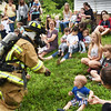 BRYAN EATON/Staff photo. The Emma Andrews Library and Community Center hosted a children's safety program led by a crew from the Newburyport Fire Department on Thursday morning. Firefighter Wendy Kimball got into full gear to show what equipment they use, though a few of the younger audience members were't sure what to make of it.