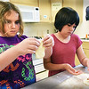 BRYAN EATON/Staff photo. Madi Grimes, 10, left, shapes her pizza dough as Savannah Crissinger, 10, puts pepperoni on her pizza at Chef's Club, one of Amesbury Youth Recreation's Summer Programs unit. The course was this week and taught by Emily White where the youngsters are also making pesto pasta, chicken cutlets and crepes with Nutella.