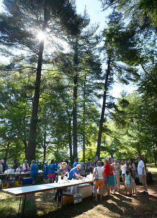 BRYAN EATON/Staff photo. Sunlight filters through the pines as people line up for breakfast at Amesbury Days' Pancake Breakfast in the Pines at the Amesbury Town Park on Tuesday.