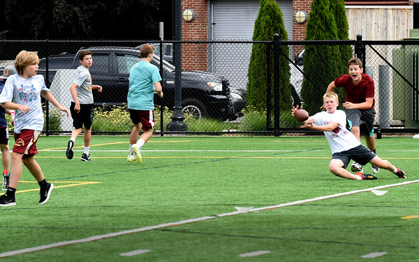 BRYAN EATON/Staff photo. Youngsters play in a football camp at Stehlin Field part of Newburyport Youth Services summer program. The camp is being coached by Newburyport High School's new head coach Ben Smolski.