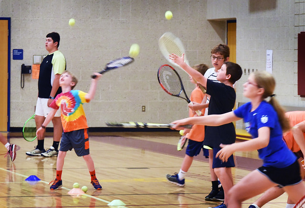 BRYAN EATON/Staff photo. Tennis balls were flying everywhere in the Bresnahan School gymnasium on Thursday morning as youngsters take lessons in the Newburyport Youth Services summer program. They usually meet at Atkinson Common, but the wet courts brought them inside.