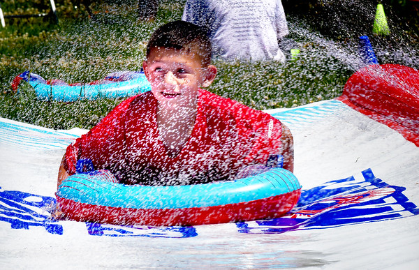 "BRYAN EATON/Staff photo. Callen Huberdeau, 7, of Amesbury moves through a waterslide after crawling through some mud among other stations. He was in the ""Messy Obstacle Course"" at the Boys and Girls Club in Salisbury on Wednesday morning."