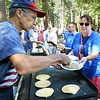 BRYAN EATON/Staff photo. Tom Hodges hands pancakes to Pauline Perris, both of Amesbury, to serve to diners for the Amesbury Days' Pancake Breakfast in the Pines. The event is sponsored by the Rock Church Ministry which they are members.
