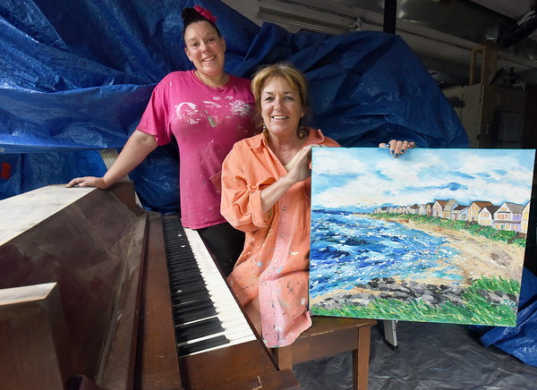 BRYAN EATON/Staff photo. Jess Cruz, left, of J.L. Cruz is sanding and priming this piano which artist Sandra Morrissey will be painting in a theme of the art she's showing. The piano will be put into Amesbury's Market Square.