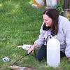 BRYAN EATON/Staff photo. Rachel Mayer uses a solution to clean off a stone at the Newbury First Parish Burying Ground.
