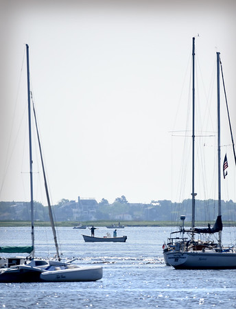 BRYAN EATON/Staff photo. Fisherman cast their lines in the Merrimack River neart the American Yacht Club in Newburyport on Saturday. Photo was taken from the town pier on Ring's Island in Salisbury.