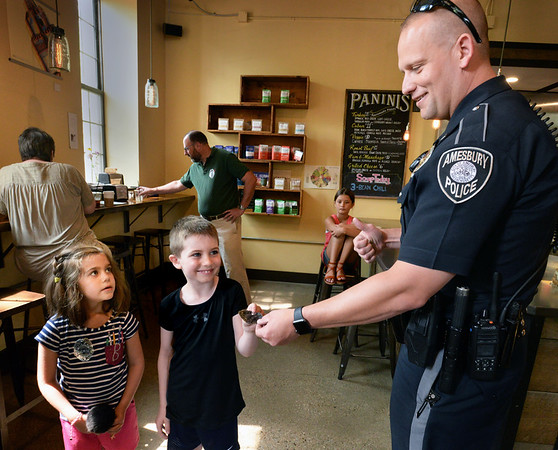 BRYAN EATON/Staff Photo. Amesbury police officer Troy Burrell hands Hunter Gauthier, 7, an honorary police badge as his sister Riley, 6, is wearing hers at Coffee WIth Cops at the Market Square Bakehouse on Wednesday morning. The event, sponsored by the Amesbury Police Department, the Bakehouse and Divine Salon and Spa, allowed the public to approach the department in a casual setting to bring up any concerns and ask questions and get to know the officers that were on hand.