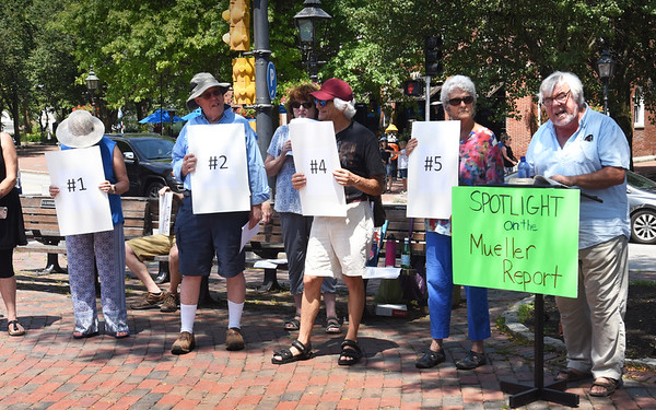 BRYAN EATON/Staff Photo. Jack Garvey, right, was one of several people reading portions of the Mueller Report in Market Square in Newburyport early Sunday afternoon.