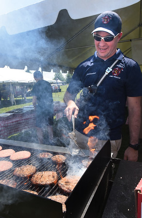 BRYAN EATON/Staff Photo. West Newbury Fire Company's Jason Goldweber is used to dealing with flames, but here they were under control while cooking hamburgers at the food tent.