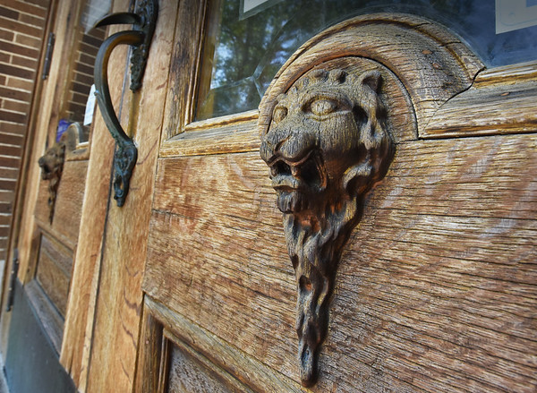 BRYAN EATON/Staff Photo. One of the two well-weathered carvings of lions on the front doors of the Amesbury Public Library.