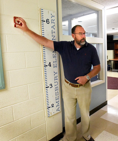 BRYAN EATON/Staff Photo. Amesbury schools Superintendent Jared Fulgoni pointed out safety concerns on a tour of Amesbury Elementary School with new principal, Shannon Noland, and buiding committee member Peter Hoyt. Here he shows a fire alarm much too high fot small students to pull.
