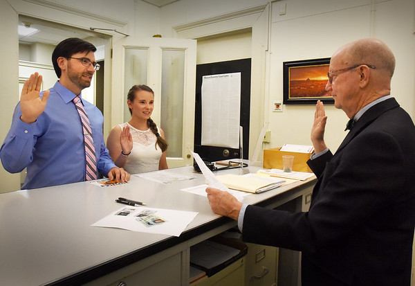 BRYAN EATON/Staff Photo. Newburyport City Clerk Richard Jones oversees an oath that there are no legal impediments to the marriage of Christoper Falcos and his fiance Elizabeth Burke Jones Thursday night. The bride happens to be the city clerk's daughter and she still had to show her drivers license, along with her soon-to-be husband, and paid the $30 fee.
