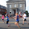 BRYAN EATON/Staff Photo. Runners are a blur as they run past the Custom House Maritime Museum.