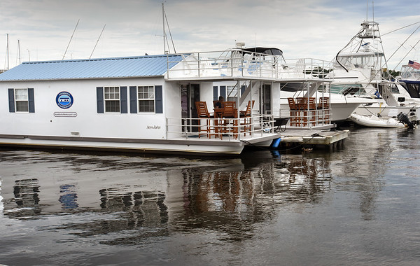 BRYAN EATON/Staff Photo. Two of the houseboats are docked behind the old Black Cow restaurant on the Merrimack River.