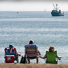 BRYAN EATON/Staff Photo. A fishing vessel comes rather close to shore in view of people at Salisbury Beach, perhaps the whales off shore sending fish closer inland. The beaches should be much busier this weekend as the temperature could hit close to 100 degrees.