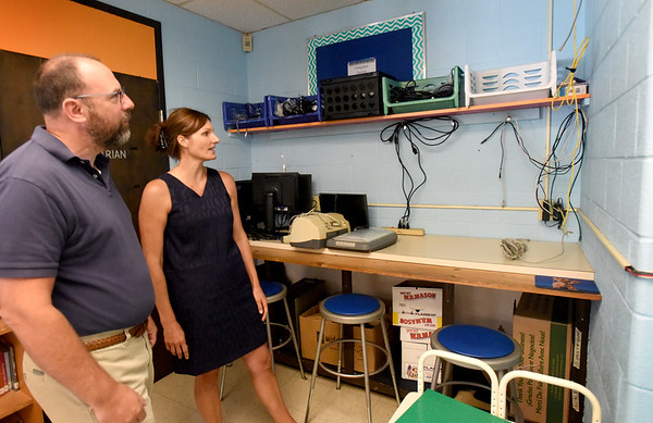 BRYAN EATON/Staff Photo. Amesbury schools Superintendent Jared Fulgoni and Principal Shannon Nolan look various computer wires and electrical strips. Newer schools have internet connections built into the walls and more electrical outlets.
