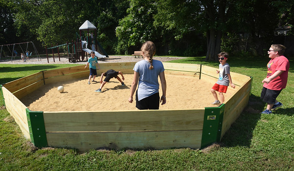 BRYAN EATON/Staff Photo. Youngsters at the Boys and Girls Club in Salisbury play in their new Gaga Ball pit near the playground. Gaga is a  sport played in an octagonal pit and is a kinder, gentler version of dodge ball, the game being played with a soft foam ball, and combining the skills of dodging, striking, running, and jumping, while trying to hit opponents with the ball below the knees.