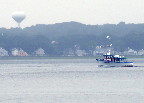 BRYAN EATON/Staff Photo. With seagulls hovering overhead, a party boat heads east in the Merrimack River with the March's Hill water tower in back. Photo was taken from Salisbury Beach State Reservation on Monday afternoon.