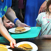 BRYAN EATON/Staff photo. Aidan Fitzsimmons, 3, with his sister, Nora, 6, has his eye on the pancakes Debra Damren is passing out. They were at the Amesbury Days event Pancakes in the PInes on Thursday put on by the Rock Church.