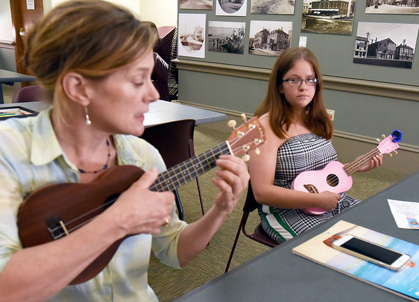 BRYAN EATON/Staff Photo. Julie Stepanek, left, of Amherst travels to different libraries teaching the fundamentals of ukulele playing, how to tune, strum and read chords then play some easy songs. Here she works with Lorelai MacIntosh and several others at the Newburyport Public Library on Tuesday afternoon.