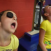 "BRYAN EATON/Staff Photo. Izabella Herr, left, of Amesbury and Hailey Cribben, of Newburyport, both 9, try to move an Oreo cookied from their forehead into their mouths at the Boys and Girls Club on Monday afternoon. They were in the ""Face the Cookie Minute to Win It Challenge."""