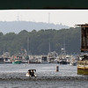 BRYAN EATON/Staff photo. A pleasure boat heads up the Merrimack River under the Route One Gillis Bridge in Newburyport as Powow Hill in Amesbury is seen in the hazy distance. It hit 90 degrees but an onshore wind cooled things off as far inland as downtown Newburyport on Wednesday afternoon.