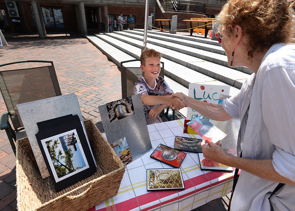 BRYAN EATON/Staff Photo. Leslie Novak of Newburyport thanks Luc Bickel, 12, after buying a photograph from him. The young photographer was part of the Inn Street Artisans Revival.