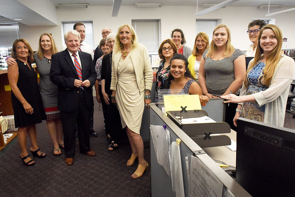 BRYAN EATON/Staff Photo. Newburyporg District Court Clerk Magistrate Kathryn Morris Early, center, has her photo taken by a colleague with other office staff including Judge Allen Swan. Wednesday was her last day in the job she started 38 years ago in the Ipswich District Court.