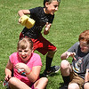 """BRYAN EATON/Staff Photo. Bode Dudgeon unloads water from a sponge onto his sister, Willa, in a game of Duck, Duck, Squirt where younsters tap the heads of those sitting in a circle and squeezed the water on the next person to become """"it."""" They were at the Youth Park Program at Amesbury Town Park where they'll be doing more water games as the weather warms throughout the week."""