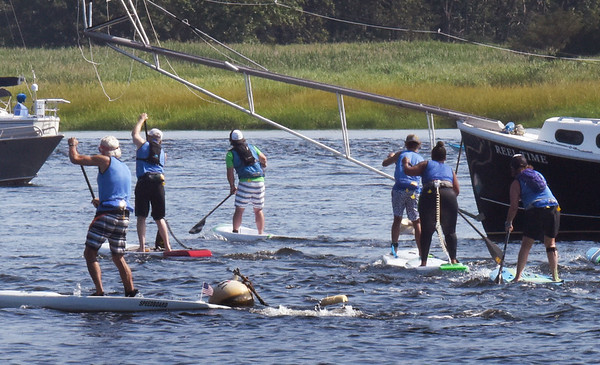 BRYAN EATON/Staff Photo. Stand up paddleboarders fight an outgoing tide as they head up the Merrimack River.