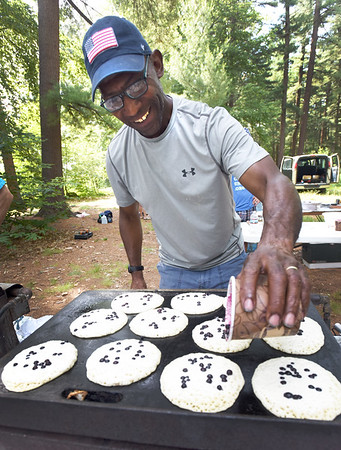 BRYAN EATON/Staff photo. Alan Boswell of the Rock Church in Amesbury sprinkles blueberries onto pancakes on the griddle at the Amesbury Days event Pancakes in the PInes on Thursday. It was one of the events for the last day of festivities ending with the fireworks at Woodsom Farm.