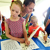 BRYAN EATON/Staff Photo. Katie Angis looks on as her children Clara, 8, left, and Ryan, 5, learn to write with quill pens. They were in the children's tent that had various historical activities at the West Newbury Bicentennial Field Day at Pipestave Hill on Saturday.