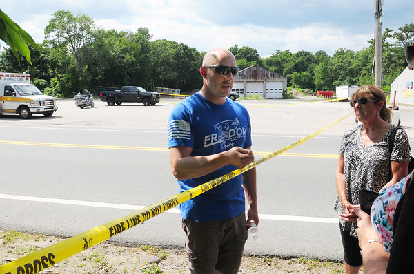BRYAN EATON/Staff Photo. Sam Racioppi explains the situation to people who work nearby his home and some neighbors who couldn't pass the police tape.