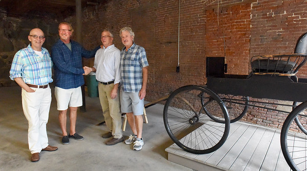 BRYAN EATON/Staff Photo. ARC Technology founder Dan Healey has donated $100,000 to the Amesbury Carriage Museum which will be housed in the lower part of Amesbury Industrial Supply. From left, museum president Peter Hoyt, Healey, museum executive director John Meyer and building owner Gregg Jardis.