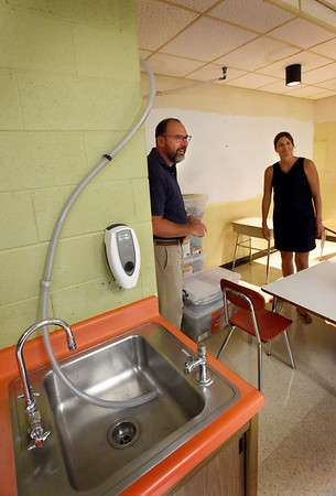 BRYAN EATON/Staff Photo. Amesbury schools Superintendent Jared Fulgoni and Principal Shannon Nolan show off a classroom that has regular leaks and is collected and drained right into this sink.
