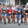 BRYAN EATON/Staff Photo. Contestants carry trays of glasses of water in the start of the Waiter/Waitress Race.