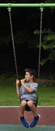BRYAN EATON/Staff Photo. Owen Mongeau, 10, hangs on a swing with a popsicle at the Bresnahan School during Popsicle Day for the YWCA of Greater Newburyport 's EPIC Summer Camp on Wednesday morning. The children were taking it easy as they had a very active day at Canobie Lake Park on Tuesday.